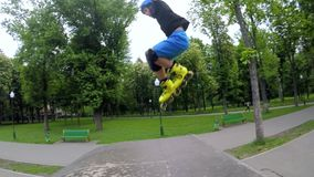 Kids extreme leisure rollerblader jump ramp park. Kids extreme leisure. Rollerblader jumping over the ramp in a park stock video