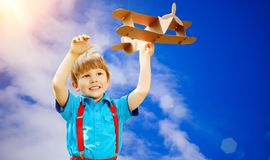 Kids fantasy. Child playing with toy airplane against sky and cl Stock Photography