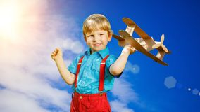 Kids fantasy. Child playing with toy airplane against sky and cl Royalty Free Stock Photography