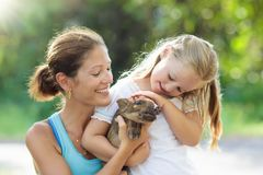 Kids and farm animals. Child with baby pig at zoo. Kids play with farm animals. Child feeding domestic animal. Young mother and little girl holding wild boar stock photo
