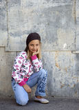 Kids Fashion. Outdoor photo of female child fashion model in fronmt of grunge wall Royalty Free Stock Photography