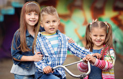 Kids, fashion concept. Portrait of happy fashion little kids having fun by painted wall Stock Photos