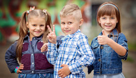 Kids, fashion concept. Portrait of happy fashion little kids having fun by painted wall Stock Photo