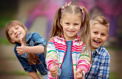 Kids, fashion concept. Portrait of happy fashion little kids having fun by painted wall Stock Image