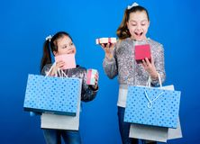 Kids fashion. Girls sisters friends with shopping bags blue background. Every product delivered to you. Shopping and stock photography