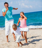 Kids and father playing on the beach Stock Photo