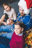 Kids and father tied up with garland Stock Image