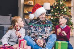 Kids and father tied up with garland Stock Photos