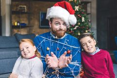Kids and father tied up with garland Royalty Free Stock Photo