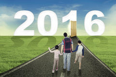 Kids and father walking toward numbers 2016 Royalty Free Stock Images