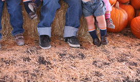 Kids feet. Many kids lined up sitting with their feet hanging and dangling with pumpkins in the background and hay in the foreground at halloween royalty free stock photos