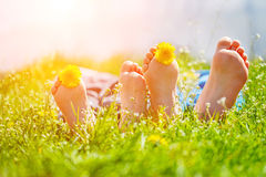 Kids feet with dandelion  flowers lying on green grass in sunny Stock Photo