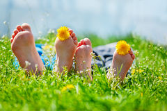 Kids feet with dandelion  flowers lying on green grass in sunny day. Concept happy chidlhood. Stock Images