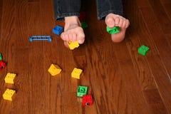 Kids feet pickup up blocks Royalty Free Stock Photography