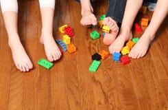 Kids feet pickup up blocks. Three pairs of childrens feet playing with blocks Royalty Free Stock Photo