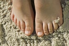 Kids feet in sandy beach fun. A child's feet in sandy beach stock images