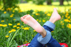Kids feet on the sunny meadow with yellow dandelion flowers Stock Image