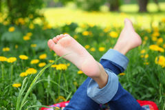 Kids feet on the sunny meadow. With yellow dandelion flowers Stock Photos