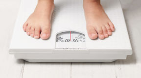 Kids feet on white weight scale. Kids feet stand on white weight scale royalty free stock photos