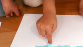 Kids finger painting on sheets of paper. In slow motion stock video footage