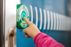 Kids finger pushing green round touch button with arrows. Transparent door between carriages in intercity train. Modern sensot. Technologies stock photos