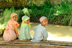 Kids Fishing. Outdoor portrait   happy Indonesian kids fishing in a pond Stock Image