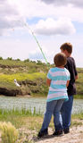 Kids Fishing. Young children fishing at the edge of a river with a small fish on the line Stock Image