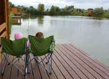 Kids are fishing. Boy and girl are fishing sitting in outdoor chairs on jetty Royalty Free Stock Photos