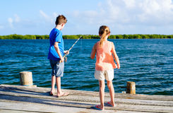 Kids  fishing. Kids brother and sister fishing together from wooden jetty Stock Photography