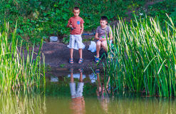 Kids fishing. Children look at the float, catching fish on the lake at sunset Stock Images