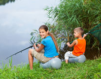 Kids fishing at the river Stock Photo