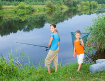 Kids fishing. Summer vacation - Sister and brother fishing at the river Stock Image