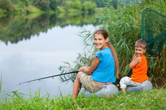 Kids fishing. Summer vacation - Sister and brother fishing at the river Stock Photography