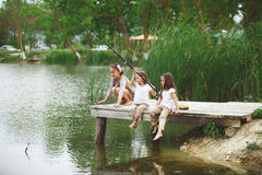 Kids fishing. Tree children fishing in pond in summer Royalty Free Stock Images
