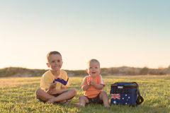 Kids with flag of Australia. Smiling kids sitting on grass at sunset and with Australian flag and cooler box stock image