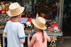 Kids at flea market. Back view of two kids brother and sister at flea market stock photography