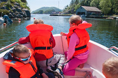Kids floating in a boat. The horizontal picture of the kids in lifejackets floating in a boat royalty free stock photo