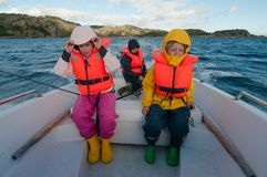 Kids in a floating boat wearing the life vests Royalty Free Stock Photos