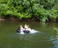 Kids floating on the river Stock Photography