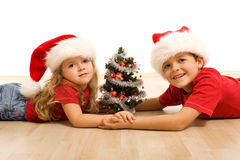 Kids on the floor with a decorated tree Royalty Free Stock Photos
