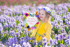 Kids with flowers and chalk board Royalty Free Stock Photography