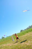 Kids flying kites high up. Two kids flying kites on the summer meadow Stock Photo
