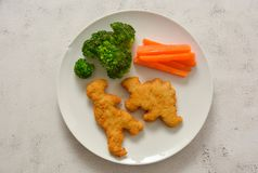 Kids food. nuggets with vegetables. Dinosaur shaped chicken, fish or turkey nuggets, ready to eat stock images