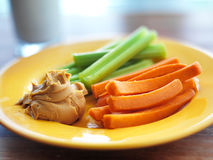 Kids food - peanut butter with celery and carrots. Peanut butter with celery and carrots and glass of milk stock images