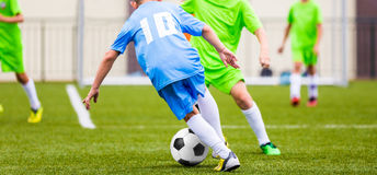 Kids Football Match. Boys Kicking Football Ball on Sports Field. Boys Kicking Football Ball on Sports Field. Soccer Game for Youth Teams Royalty Free Stock Photo