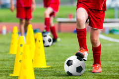Kids Football Soccer Training.Young Athlete with Football Ball. On Pitch. Child in Red Soccer Uniform Kicking Ball. Boy Practice Dribbling Drills on Sport Grass Stock Image