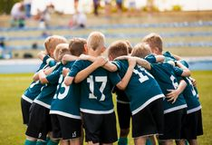 Kids football team building team spirit. Soccer children team in huddle. Group of boys united before the final soccer match royalty free stock photos
