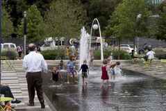 Kids in a fountain and parents watching them Stock Image