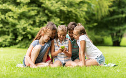 Kids or friends with smartphone in summer park Royalty Free Stock Image