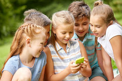 Kids or friends with smartphone in summer park. Friendship, childhood, technology and people concept - group of happy kids or friends with smartphone in summer Royalty Free Stock Image